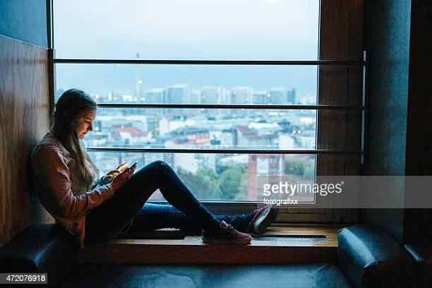 Giovane donna è in smartphone, illuminato sullo skyline della città sullo sfondo