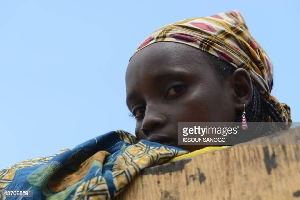 A young woman looks on while sitting atop a vehicle loaded with people and goods part of a convoy of vehicles carrying Muslims from the PK12 district...