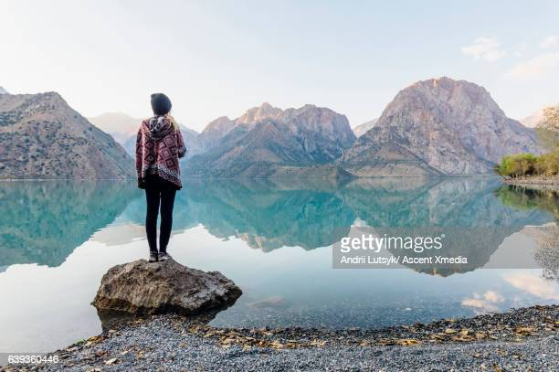 Young woman looks out across mountain lake