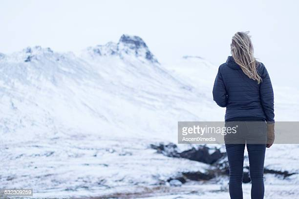 Young woman looks out across snowy mtn landscape