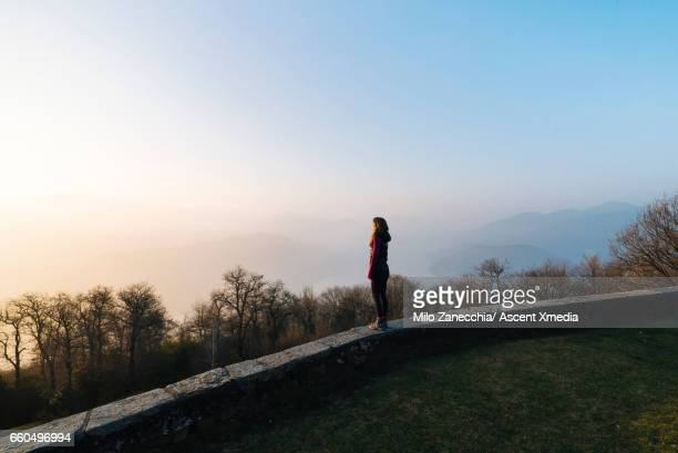 Young woman looks out across valley from stone wall
