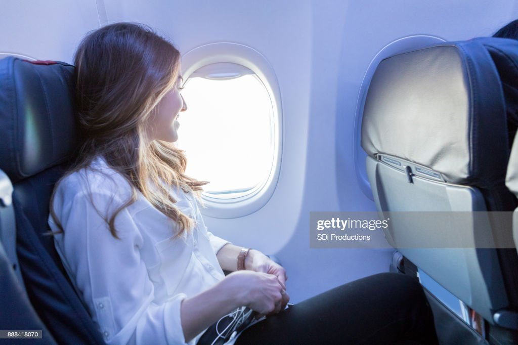 Young woman looks out aircraft window during flight : Stock Photo