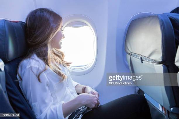 Young woman looks out aircraft window during flight