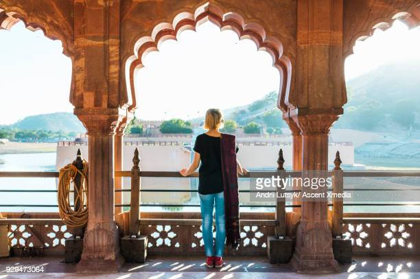 Young woman looks out at Amer Fort in morning light, Jaipur