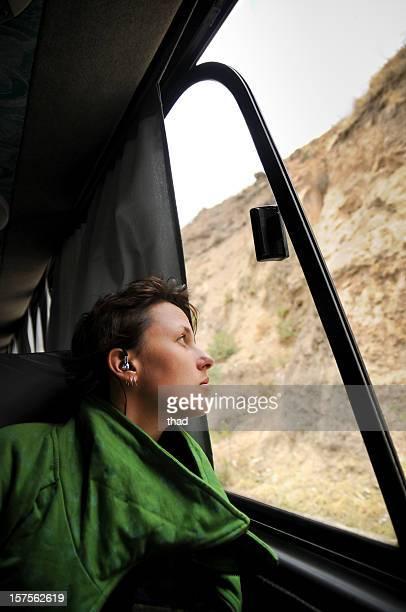Jeune femme regarde par la fenêtre de