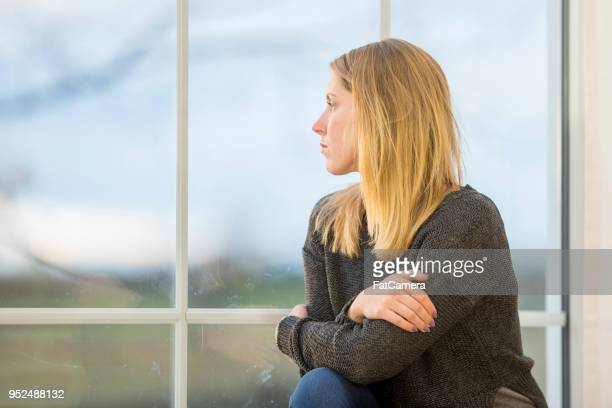 young woman looks out the window pensively - suicide stock photos and pictures