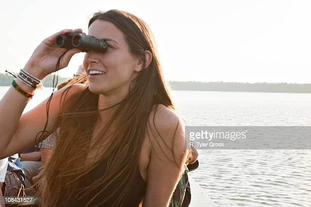 A young woman looks through binoculars at various types of birds on lake Sandoval in the amazon rainforest.