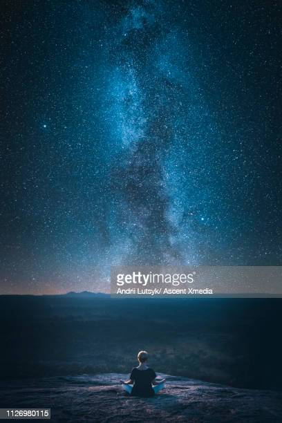 young woman looks up at galaxy from mountain top - star field stock pictures, royalty-free photos & images