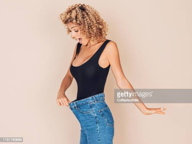 young woman losing weight - derrota imagens e fotografias de stock