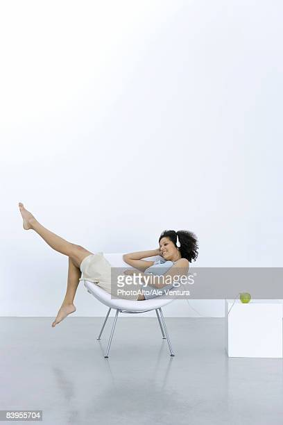 Young woman lounging in chair, listening to headphones connected to apple
