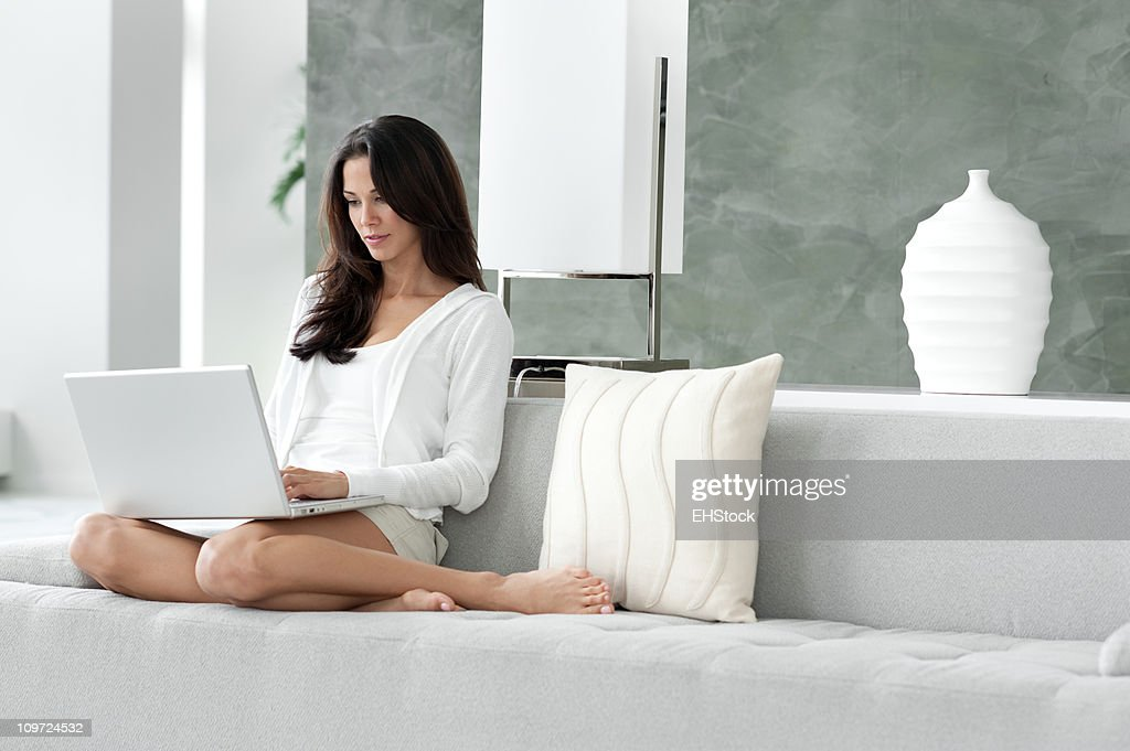 Young Woman Lounging in Living Room on Couch with Laptop : Stock Photo
