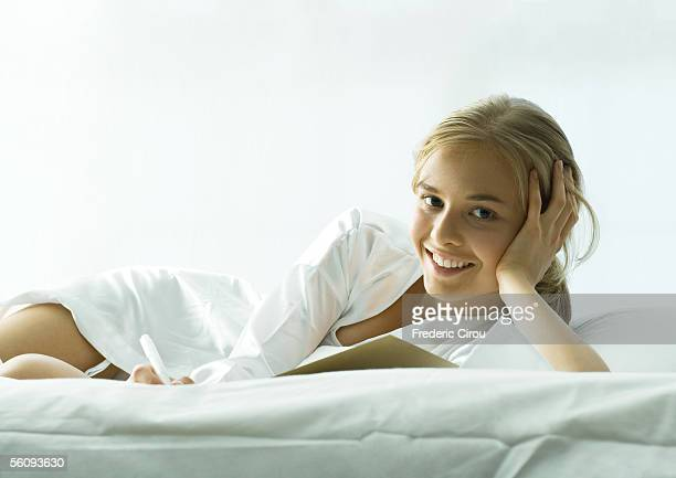 young woman lounging on bed - women in slips stock pictures, royalty-free photos & images