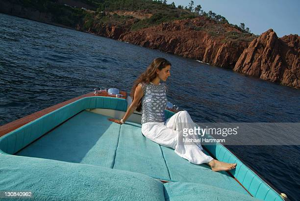 Young woman lounging on the deck of a Riva Motorboat, Théoule-sur-Mer, France, Europe