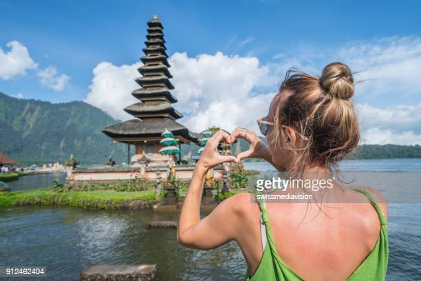 Young woman loving ancient temple in Bali, Indonesia
