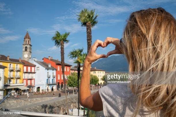 Young woman loving Swiss village in Ascona, Ticino, Switzerland making heart shape frame with hands