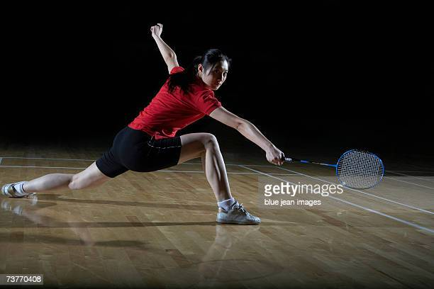 Young woman lunges to her left and extends her racket, preparing to return a shot during a game of badminton.