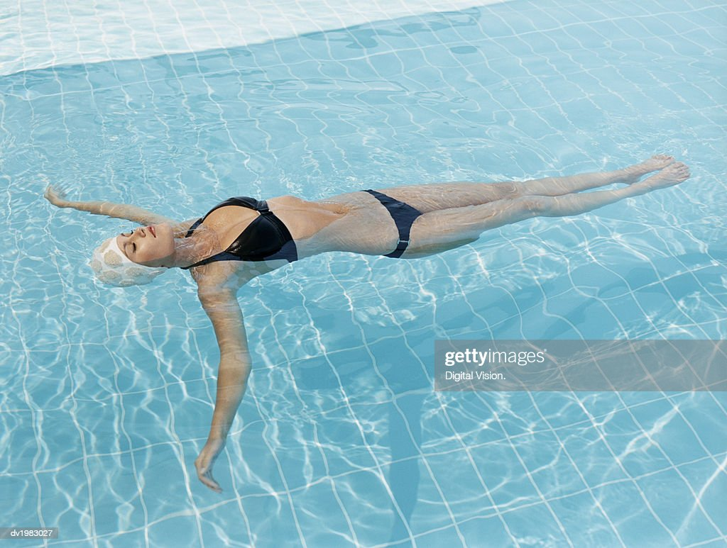 Young Woman Lying Afloat in a Swimming Pool With Her Eyes Closed : Stock Photo
