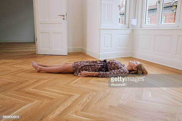 Young woman lying alone on floor in an empty room