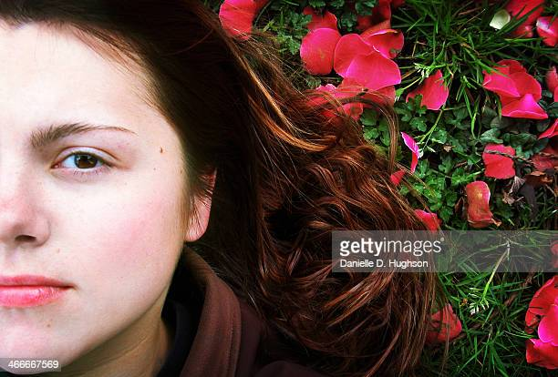 Young Woman Lying Among Red Flower Petals