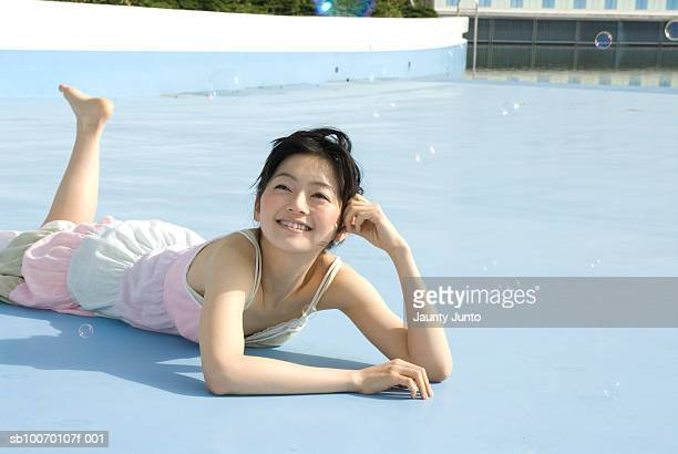 young woman lying and looking at bubbles, smiling - 腹ばい ストックフォトと画像