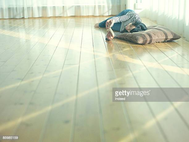 young woman lying and reading on floor - simple living stock pictures, royalty-free photos & images