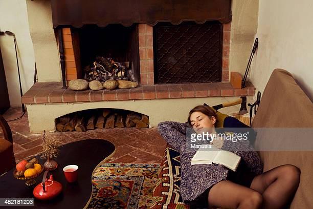 young woman lying asleep on sofa with her book - junge frau strumpfhose stock-fotos und bilder
