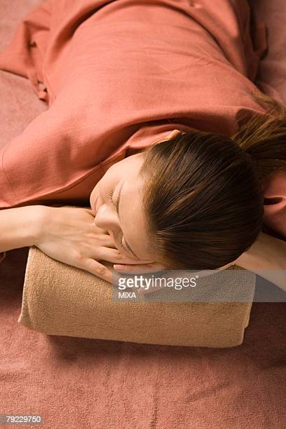 Young woman lying at bedrock bath