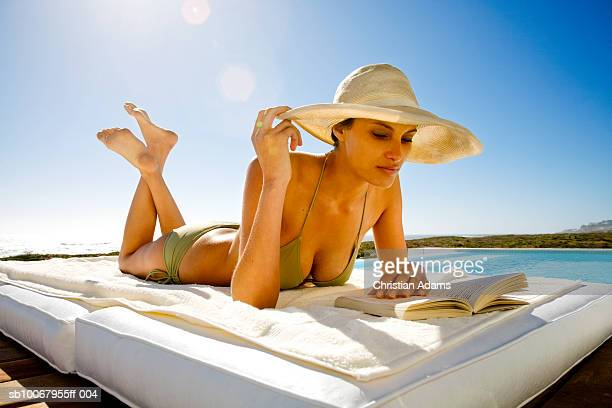 Young woman lying at poolside, reading book