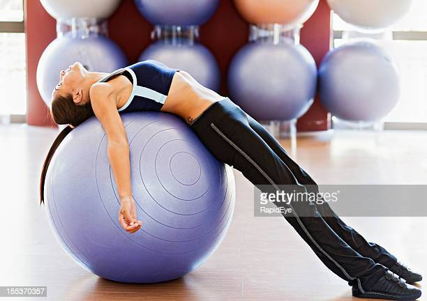 Young woman lying back on exercise ball in gym