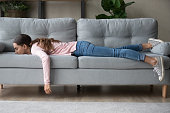 Young woman lying buried her face in sofa feels tired