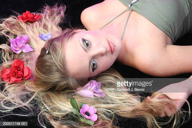 young woman lying down, hair covered in flowers, elevated view - bavosi stock photos and pictures