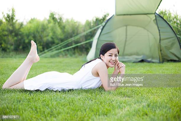 Young woman lying down in grass