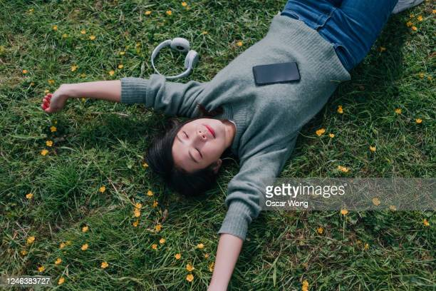 young woman lying down in meadow with smartphone and headphone - social media stock pictures, royalty-free photos & images