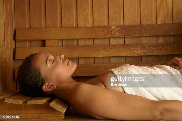 young woman lying down in sauna - black woman in sauna stock pictures, royalty-free photos & images
