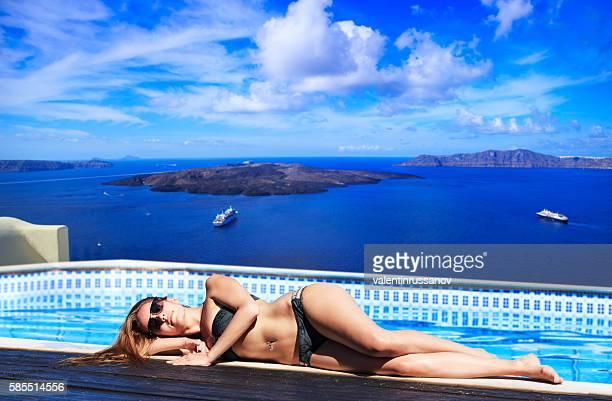 Young woman lying down near swimming pool in Santorini