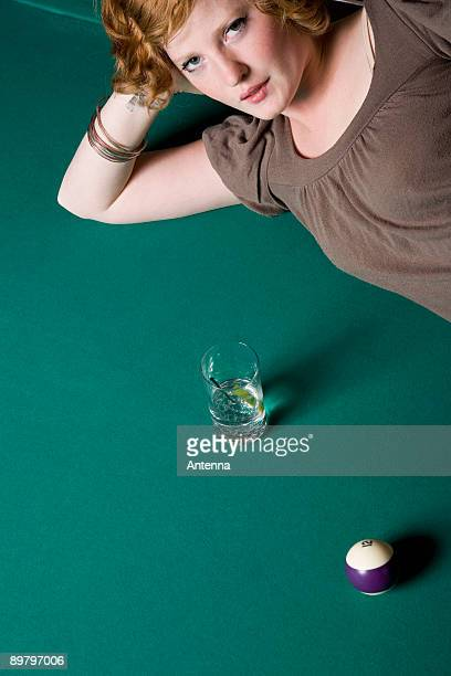 A young woman lying down on a pool table