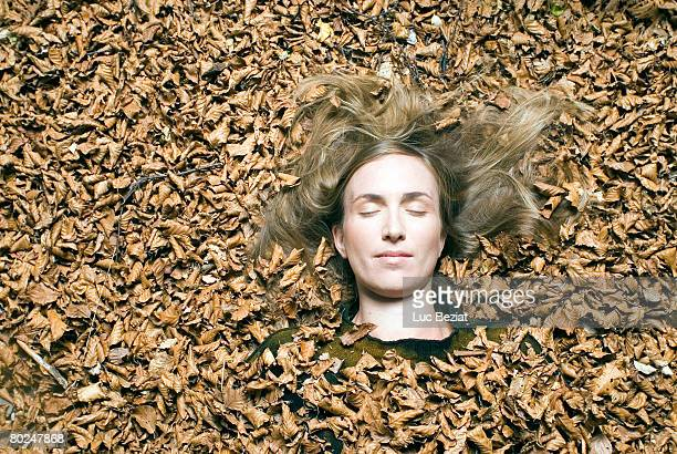 young woman lying down on leafs. - 埋まる ストックフォトと画像