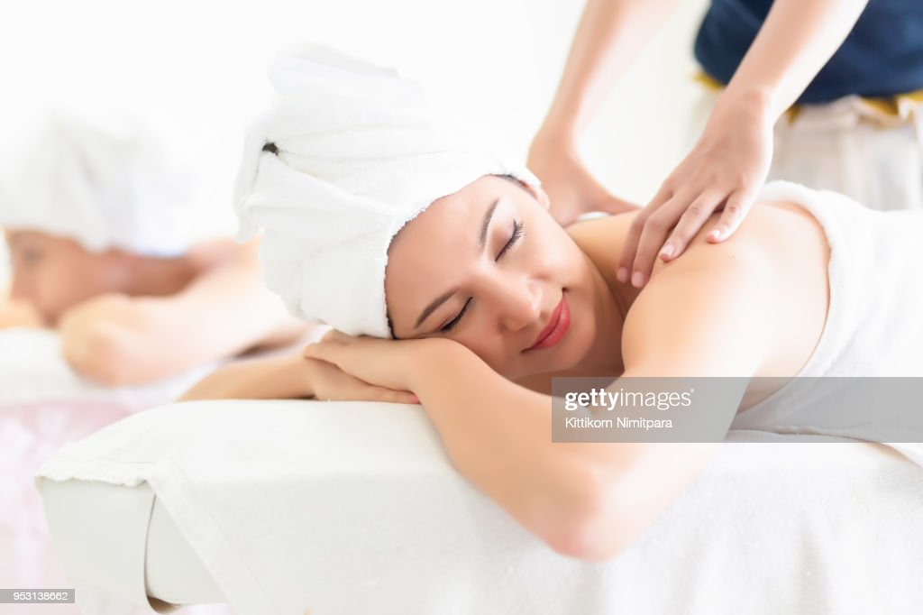 Young woman lying down on massage beds at Asian luxury spa ,Healthy and  vacation concept