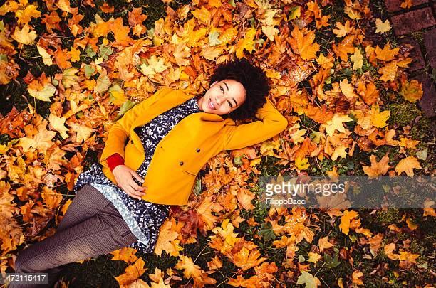 Jeune femme allongée sur feuilles jaunes