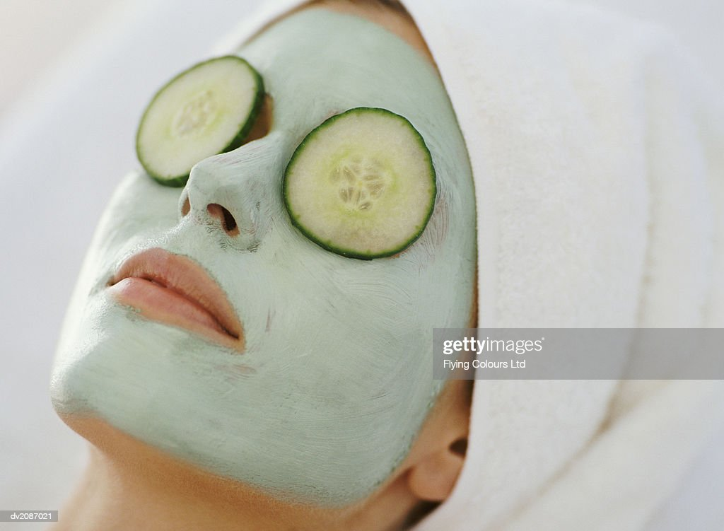 Young Woman Lying Down With a Face Pack and a Towel Wrapped Around Her Head : Stock Photo