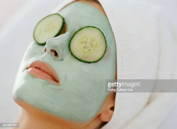 young woman lying down with a face pack and a towel wrapped around her head - gurke stock-fotos und bilder