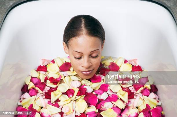 Young woman lying in a bathtub with flower petals