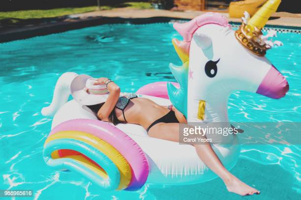 young woman lying in a big unicorn inflatable ring at pool in summer - unicorn stock pictures, royalty-free photos & images
