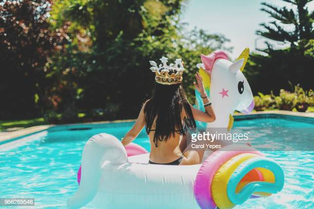 young woman lying in a big unicorn inflatable ring at pool in summer