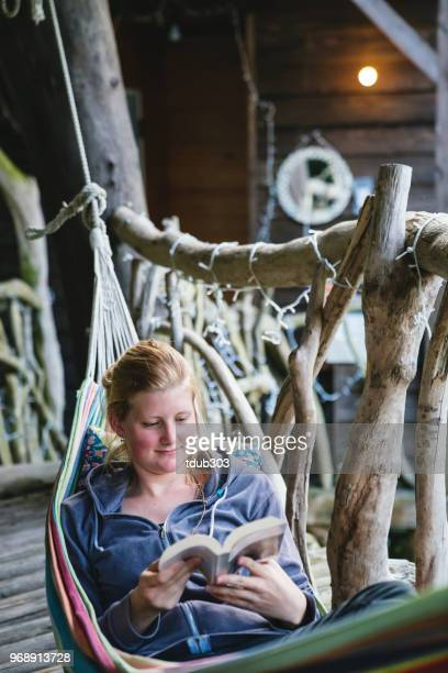 Young woman lying in a hammock reading a book in a treehouse