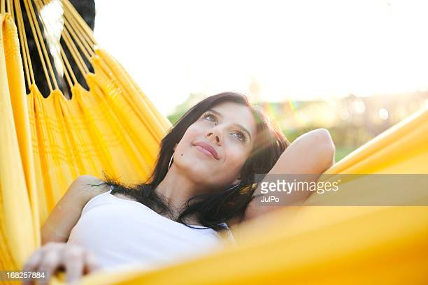 Young woman lying in a yellow hammock