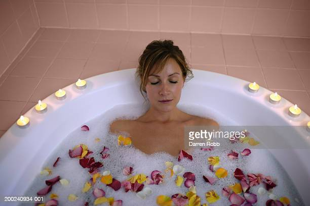 young woman lying in bath with rose petals and candles, elevated view - bubble bath stock pictures, royalty-free photos & images