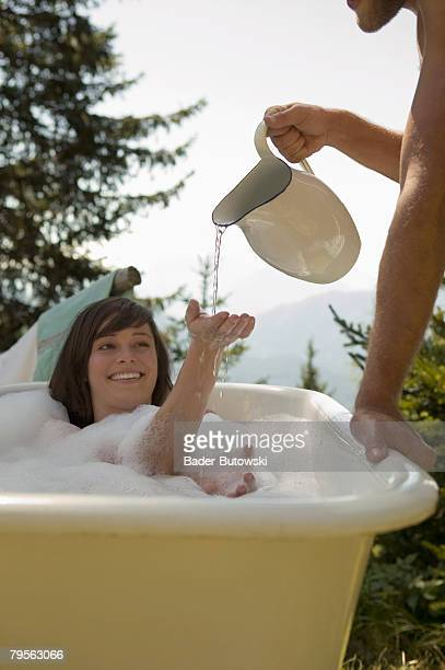 'Young woman lying in bathtub, young man pouring water, outdoors'