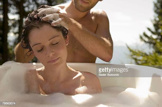 Young woman lying in bathtub, young man washing hair