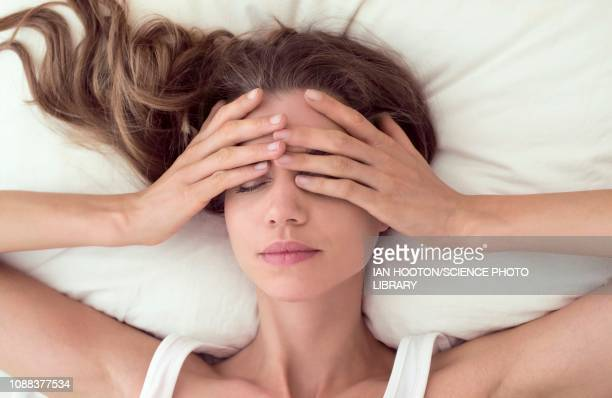 young woman lying in bed and covering eyes - jet lag stock pictures, royalty-free photos & images